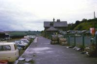 The final station on the L&SWR route to Cornwall was the fishing town of Padstow on the River Camel. The town lost the former L&SWR connection in October 1966, however services did continue until the end of January 1967 from Bodmin. The photo (looking east towards Wadebridge) shows the station building and platform only 30 months after services had finished. The trackbed has already taken over as a car park and the station building looks like it has been taken over by the local bus company. On the extreme left of the photo is the fish shed where refrigerated railway wagons were loaded up to be taken to fish markets in the south of England.<br><br>[John McIntyre&nbsp;/07/1969]