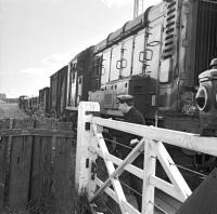 The level crossing to the east of Earlston station, seen here on 16 July 1965, as the crossing gates are opened by the <I>second man</I> to allow passage of the last returning freight along the branch. Official closure date for the line was three days later on Monday 19th July 1965.<br> <br><br>[Bruce McCartney&nbsp;16/07/1965]
