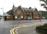 View west across the A711 St Mary's Street, Kirkcudbright on a rainy afternoon in August 2009. The stately old building is the 1864 terminus of the Kirkcudbright Railway. The main  part of the old station (closed in 1965) now houses a <i>Beauty and Fitness Studio</i>, while the small structure on the corner of the block, once the station toilets,  is now the home of the local bookies. (Subliminal message there perhaps?)   <br> <br><br>[John Furnevel&nbsp;31/08/2009]