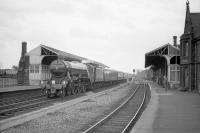 4472 <I>Flying Scotsman</I> runs north through Tweedmouth station on 9 May 1964 with <I>Pegler's Pullman</I> en route from Doncaster to Edinburgh. Tweeedmouth shed (52D) can be seen in the rear right of the photograph. The locomotive spent the following 9 days in Scotland on railtour duty and returned south light engine on 18 May. It was during this visit that the initial work on the Terence Cuneo painting of 4472 on the Forth Bridge was undertaken. <br> <br><br>[Robin Barbour Collection (Courtesy Bruce McCartney)&nbsp;09/05/1964]