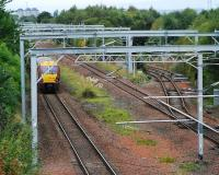 An Ayr service heads west at Cardonald Junction. The junction has not yet been re-laid for the third track but the overhead line equipment is a strange mixture of replaced (across all tracks) and old. The line on the right serves Deanside Transit.<br><br>[Ewan Crawford&nbsp;26/09/2009]