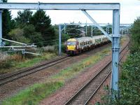 A service heads west from Hillington West. The photograph was taken to show the new overhead equipment laid in to allow the tripling of the railway. There were former sidings to the right of the existing line.<br><br>[Ewan Crawford&nbsp;26/09/2009]