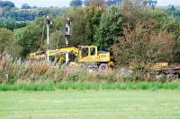 A Hydrex road-rail crane makes some slight adjustments at Lugton before a Tamper moved in. Lugton is the north end of the new loop which runs north from Stewarton. There was until recently just a short loop here (and the disused line to Giffen).<br><br>[Ewan Crawford&nbsp;26/09/2009]