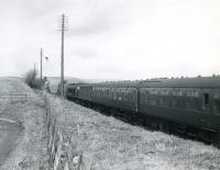 A Leeds - Glasgow train heads north at Lugton behind a <I>Peak</I> in March 1966. The locomotive is about to pass between the abutments of the overbridge that once carried the Lanarkshire and Ayrshire Railway over the formation at this point.<br><br>[Colin Miller&nbsp;/03/1966]