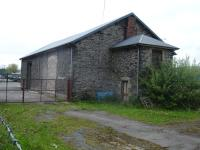 Former railway goods shed still in use alongside A5 trunk road to west of Corwen Station, with one loading door stoned up and full height roller shutter door fitted at far end.  <br><br>[David Pesterfield 07/05/2009]