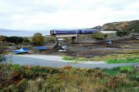 The morning service from Inverness passes south through Erbusaig with only a short distance left to reach Kyle of Lochalsh. The train came through the narrow cleft in the cliff above the right hand side of the right carriage. There are signs of recent embankment stengthening works. The view looks towards the Crowlin Islands. <br><br>[Ewan Crawford&nbsp;01/10/2009]
