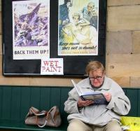 <I>The enthusiast #2.</I>  A passenger awaiting the next NYMR train to Whitby at Pickering on 12 October 2009 appears to be engrossed in a recent purchase from the station bookshop. The WWII posters in the background are part of the preparations for the annual <I>1940s Wartime Weekend</I> held locally. (The book in question is <I>Historic Steam Boiler Explosions</I> by Alan McEwen.)  <br> <br><br>[John Furnevel&nbsp;12/10/2009]
