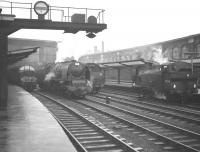 Scene at the south end of a rain soaked Carlisle station on 28 December 1963. From left to right are D323 with a Glasgow - Liverpool train, 46240 <I>City of Coventry</I>, the tender of 46225 <I>Duchess of Gloucester</I> and 47326, the station pilot.<br><br>[Robin Barbour Collection (Courtesy Bruce McCartney)&nbsp;28/12/1963]