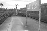 Looking north from Dumfries in 1965 with a Peak - hauled service (possibly the <I>Thames-Clyde Express</I>) pulling away from the platform. [See image 39421]<br> <br><br>[Colin Miller&nbsp;//1965]
