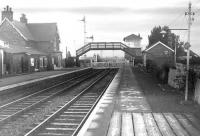 Platform view south over the level crossing at Longtown around 1962. (The footbridge and signals controlling the junction with the single line link to Mossband shown in the later mystery photograph [see image 5986] can be clearly seen here).  <br> <br><br>[Robin Barbour Collection (Courtesy Bruce McCartney)&nbsp;//1962]