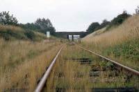 Further to Ken Strachan's picture of the Witham-Maldon line trackbed today [see image 26138], here is the corresponding scene from approximately the same spot on 28th August 1977. The road bridge is the point of comparison. The sign on the left warns industrial rail traffic from the Rom River factory beyond the bridge that it must not pass through the gates (behind the photographer) that mark the beginning of British Rail jurisdiction.<br><br>[Mark Dufton&nbsp;28/08/1977]