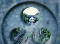 A DMU approaches Great Malvern from the Birmingham direction in 1988. Seen through the decorative stone parapet on the road bridge.<br><br>[Ken Strachan&nbsp;//1988]
