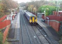 A Clitheroe to Manchester Victoria service calls at Ramsgreave and Wilpshire, a station that only opened when services to Clitheroe resumed in 1987. It is better sited for the local population than the original Wilpshire station, closed in 1962, which is the white building in the distance, [See image 19311] now a private residence.  <br><br>[Mark Bartlett&nbsp;17/11/2009]