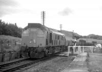 An Inverness-bound freight passes through the open level crossing at Bunchrew in 1970. Bunchrew was one of some 16 wayside stations on the Far North Line whose closure (in June 1960) pre-dated the Beeching era. This is also the location where a Network Rail employee had a narrow escape when his car collided with a train in May 2008 (see news items).<br> <br><br>[David Spaven&nbsp;//1970]