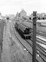 With Waterloo yard behind the camera, this view looks from Castle St road bridge towards Kittybrewster in the summer of May 1975 as a class 08 shunts a bogie bolster wagon loaded with pipes for the North Sea oil industry.<br><br>[John McIntyre&nbsp;/05/1975]