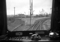 A view of the former triangular platform layout at Forres, taken from the rear of an Inverness-Aberdeen DMU on 2nd May 1968. The redundant platform to the left formerly served passenger workings from the Elgin direction to Aviemore via Dava and Grantown, the line beside it probably last being used for freight traffic prior to 1965 closure. The layout at Forres - with just a single platform - has remained virtually unchanged since then, despite regularly-voiced proposals to shift the crossing loop (the start of which can be seen in the centre-right of the photo) back into the station.<br> <br><br>[David Spaven&nbsp;02/05/1968]