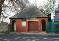 A public toilet block on Colinton Road, Edinburgh, photographed on 27 November 2009. The building, recently saved from demolition (notice the new flats currently under construction on the right), was originally a tram ticket office standing alongside the Colinton terminus of the no 9 and no 10 tram routes [see image 26504]. The ticket/enquiry counter was behind the double doors. The building is thought to be the last of its type and is now listed as being of historical importance.<br> <br><br>[John Furnevel&nbsp;27/11/2009]