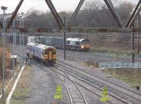 Framed by a gantry used to carry cables over the line, a York to Blackpool Sprinter joins the WCML at Farington Curve Junction as a DRS container train runs south on the fast line. In the centre foreground is the line to Ormskirk.<br><br>[Mark Bartlett&nbsp;27/11/2009]