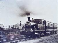 A train for Whittingham hospital leaves the CMHW station at Grimsargh behind Barclay 0-4-2T No.2 (Works No. AB 1026/1904), sometime during WWI. At this point the hospital line curved away from the Preston and Longridge line that ran behind the low wooden fence. The two passenger coaches were later replaced by three converted ex-LNWR brakevans that lasted until the end of this 'free to ride' service in 1957. The loco, new to the line from Andrew Barclay, lasted in service until 1952 and was replaced by the Sentinel shunter <I>Gradwell</I>.. <br><br>[David Hindle Collection&nbsp;//]