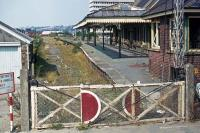 A forlorn Barnstaple Town station photographed from a rickety signal post on 8th September 1976. Although the line through here to Ilfracombe closed in 1970, its infrastructure remained in limbo as preservation attempts continued up until 1975. A final train was run that year, then the track was removed and the cause was lost. The station building remains in a restored form, as do part of the canopy and the signal box.<br><br>[Mark Dufton&nbsp;08/09/1976]