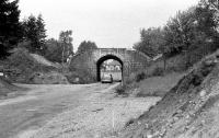 This is the rail bridge over the road at the north end of Boat of Garten during the demolition in June 1974. The embankment either side of the bridge has already been cut back prior to the removal of the arch. The road was being widened in conjunction with the new road bridge over the River Spey which was behind the camera. For several years there was a gap on the rail route from Boat of Garten to Broomhill. The original bridge was 3 tracks wide and was replaced by a single track rail bridge when the Strathspey Railway extended to Broomhill in the first years of the 21st Century.<br><br>[John McIntyre&nbsp;16/06/1974]