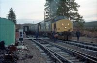 Early morning at Tulloch during Christmas 1987. The northbound sleeper, hauled by 37423, has drawn forward of the crossing between platforms due to its length. At the southbound platform is the morning train for Glasgow (37407 <i>Loch Long</i>). The train crews swap over across the tracks (they also guided a dismounting passenger). Slippery diesel was spilled all over the footway so crunching across the ballast might have been a better option anyway. Tulloch was very much in use as a maintenance base at the time, with lots of equipment lying alongside the platers hut on the left.<br><br>[Ewan Crawford&nbsp;29/12/1987]