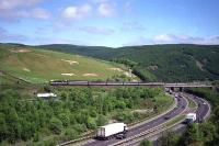 A Class 87 races north over Harthope viaduct and the A74 dual carriageway at the end of May 1992 with a service for Glasgow Central.<br><br>[John McIntyre&nbsp;29/05/1992]