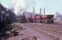 A Barclay 0-4-0ST, probably No. 1, bustles about the foundry with internal user hopper wagons on the last day of operations at Millom Ironworks in 1968. On the left a John Fowler diesel shunter busies itself with a rake of 16 tonners. After the works closed later that year all trace of the industry was quickly swept away, although the three diesel locomotives went to Workington Docks where they survived for a further forty years.<br><br>[David Hindle&nbsp;19/09/1968]