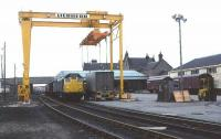 A 1977 view showing the westward expansion and modernisation of Elgin freight depot following the removal of the platforms (the Class 24 is standing in the former through platform road) after the withdrawal of the Coast and Craigellachie passenger services in 1968. For the next 25 years Elgin served as a major railhead for whisky, military equipment, oil and general freight traffic, with a mix of containerised and conventional wagon business.<br><br>[David Spaven&nbsp;//1977]