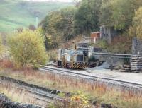 Two industrial shunters stand in the Tunstead Quarry complex with a third, possibly <I>Harry Townley</I> [See image 26162], hiding behind the trees. In the foreground is the former Midland mainline, now the freight only route to Buxton and Hindlow through the imposing Derbyshire Dales landscape.  <br><br>[Mark Bartlett&nbsp;23/10/2009]