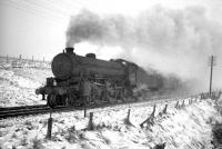 B1 4-6-0 no 61029 <I>Chamois</I> runs through falling snow as it takes a southbound freight over Whitrope summit in the sixties.<br><br>[Robin Barbour Collection (Courtesy Bruce McCartney)&nbsp;//]