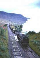 BR Standard class 9F 2-10-0 no 92009 heads south on the Settle and Carlisle line at Ais Gill in the 1960s with a mixed freight.<br> <br><br>[Robin Barbour Collection (Courtesy Bruce McCartney) //]