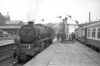 Scene at the east end of Blackburn station on 3 June 1967. The building on the left is part of the old fish dock with the former parcels depot alongside. This has since been demolished and a supermarket car park now overlooks the station [See image 22709]. Black 5 no 45339 is standing on the left, while on the right is the LCGB <I>Thames-Tyne Limited</I>, bound for Carlisle via the S&C, with Britannia Pacific no 70039 <I>Sir Christopher Wren</I> taking on water.<br><br>[Robin Barbour Collection (Courtesy Bruce McCartney) 03/06/1967]