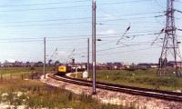 This photograph was taken looking back from a Glasgow to London train as it passed Farington Junction in June 1976. Waiting to join the WCML southbound on the curve from Lostock Hall Junction is a Class 40 and a dead electric locomotive on a freight train. Today the area to the left and right of the Class 40 is covered with housing.<br><br>[John McIntyre&nbsp;/06/1976]