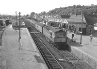 The morning train for Wick runs into Dingwall in August 1966. Note the Royal Mail coach immediately behind the locomotive and the loop platform on the left still operational at that time.<br><br>[Colin Miller&nbsp;/08/1966]