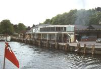 View of Lakeside pier and station in 1976 taken from a vessel on Lake Windermere. Note the overall roof and the nose of Fairburn 2-6-4T no 42085 standing at the buffer stops. The rear coaches of the train and the signal box can be seen in the left background.<br><br>[Colin Miller&nbsp;//1976]