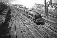 Pride of Polmadie. Stanier <I>Coronation</I> Pacific no 46232 <I>Duchess of Montrose</I>, about to pass her home shed with the up <I>Mid-Day Scot</I> shortly after leaving Glasgow Central on 16 May 1959. In the background stands the ironworks founded in 1837 by William Dixon, which became known to Glaswegians as <i>Dixon's Blazes</i> due to the blast furnaces lighting up the city skyline day and night. Production ceased the year before this photograph was taken, since when the area has been substantially redeveloped. <br> <br><br>[A Snapper (Courtesy Bruce McCartney)&nbsp;16/05/1959]