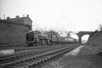 After crossing the River Eden, Britannia Pacific no 70051 <I>Firth of Forth</I> passes below the bridge carrying Etterby Road as it approaches Kingmoor with a northbound train around the mid 1960s. The Britannia was withdrawn from Kingmoor shed at the end of 1967 and disposed of through McWilliams of Shettleston in March 1968.<br><br>[Robin Barbour Collection (Courtesy Bruce McCartney)&nbsp;//]