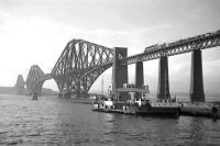 Scene at Hawes Pier, South Queensferry in June 1962 as the paddle-driven ferry <I>Robert the Bruce</I>, (with a carrying capacity of 28 cars), prepares for another crossing. One of 4 such ferries withdrawn on the opening of the road bridge in 1964, it was cut up by P&W McLellan at Bo'ness the following year.  Meantime, high above the water, a Standard Class 5 and a B1 can be seen double-heading a northbound goods train onto the Forth Bridge.<br><br>[Frank Spaven Collection (Courtesy David Spaven)&nbsp;/06/1962]