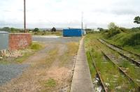 View east from Stranraer Town station in May 2007, some 41 years after closure. To the left  stood a large goods yard and locomotive shed, the surviving building of which can be seen in the centre background behind the blue container. Beyond the shed a large scrapyard occupies the 'V' between this route and the Harbour branch, which turns north west just around the curve at Stranraer Harbour Junction. Behind the camera the line once continued to Portpatrick, the last remnants of this section having been closed completely in 1959 [see image 15539].<br> <br><br>[John Furnevel&nbsp;31/05/2007]