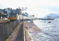 A late 1960s view of Fort William's then-classic lochside location. Opened by the West Highland Railway in 1894, the entire rail presence in this view was swept aside to accommodate the road builders, and the station was relocated in 1975 to an altogether more mundane location half a mile to the north east.<br><br>[Frank Spaven Collection (Courtesy David Spaven)&nbsp;//]