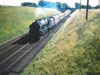 A northbound train, hauled by Holbeck based Royal Scot 46113 <I>Cameronian</I>, passing Lugton's colour light down distant signal on Saturday 22 August 1959, having just cleared the A735 road bridge. <br><br>[A Snapper (Courtesy Bruce McCartney)&nbsp;22/08/1959]
