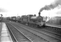 J36 0-6-0 no 65303 pulls up at Inverurie with a freight in March 1959. Immediately behind the J36 is Barclay diesel-hydraulic no D2414, at that time a recent addition to the allocation of Keith shed.<br><br>[Robin Barbour Collection (Courtesy Bruce McCartney)&nbsp;26/03/1959]