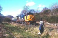 A reluctant trainspotter watches a Kyle-Inverness train drift east down the bank through Achterneed (closed 1965) heading for Dingwall in 1988.<br><br>[David Spaven&nbsp;//1988]
