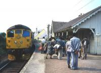 A party of academics and planners from developing countries waits to board the Inverness train at Plockton in the summer of 1983. The 'Plockton seminar' on regional development was an annual event for many years organised by the photographer, originally in his capacity as Head of Planning & Research at the Highlands & Islands Development Board.<br><br>[Frank Spaven Collection (Courtesy David Spaven)&nbsp;//]
