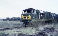 Two Hymek Class 35s and a North British Class 22 await the inevitable in Swindon Works yard in 1972. The NBL Class 22 is in early rail blue with a half yellow panel and engineless although the flat wagon next to it appears to be carrying a power unit under the tarpaulin. The green Hymek has already lost its engine and the roofless early blue specimen behind is in an equally sorry state. My records from the time indicate that the Class 22 was D6322 and the green Hymek is D7024.  <br><br>[Mark Bartlett&nbsp;18/03/1972]
