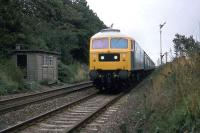 One of Stratford works characteristically painted Class 47 locomotives approaches Ardleigh level crossing at speed with a Norwich-Liverpool Street working on 25th September 1977.<br><br>[Mark Dufton&nbsp;25/09/1977]