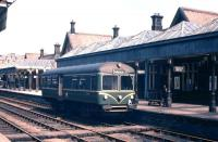 The mid-day departure for Gleneagles prepares to leave Crieff's grand and capacious station in the early summer of 1961 (once someone closes the track-side door). If ever a line which was soon to face the Beeching Axe had options for sensible cost rationalisation to avoid closure, then this was it - too many buildings, extensive platform awnings, three tracks through the station, complex signalling - all for a 'one train working' railbus service and a couple of freight trains daily. The Beeching Report actually highlighted the Gleneagles-Crieff/Comrie service as a case study, and the statistics showed that it was the track and signalling costs which killed the service. If a Crieff-Gleneagles 'basic railway' had clung on, doubtless we would now be enjoying an hourly Crieff-Glasgow service!<br><br>[Frank Spaven Collection (Courtesy David Spaven)&nbsp;//1961]