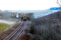 Running approximately 10 minutes late, an East Kilbride - Glasgow Central service passes under the bridge carrying the A726 on the approach to Thorntonhall on 11 February.<br><br>[John Steven&nbsp;11/02/2010]