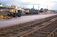 A southbound freight heads out of Invergordon in the summer of 1973. In the right background is one of the ubiquitous NCL (National Carriers) vans which distributed parcels and sundries traffic by road from six stations north of Inverness - Dingwall, Kyle, Invergordon, Brora, Wick and Thurso.<br> <br><br>[David Spaven&nbsp;//1973]
